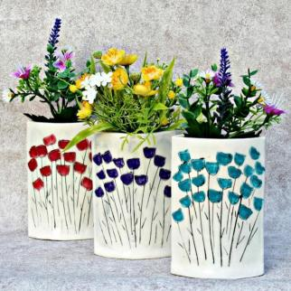 3 white vases  filled with wildflowers with sgraffito design flowers in red, purple and teal