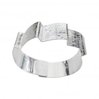 Textured silver overlapping cuff representing waves.