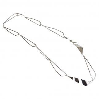 Silver linked necklace with asymmetrical formed pieces representing how waves flow around islands.