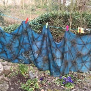 large hand dyed indigo shibori shawl drying in garden